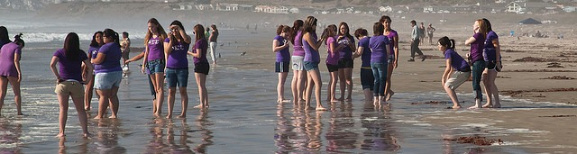 Young teen girls in purple shirts enjoy socializing on a hot day at water's edge