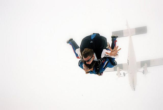 parachutist skydiving - airplane visible above him