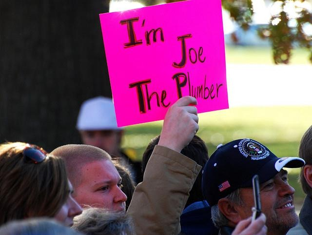 man holding a sign which reads I'm Joe The Plumber